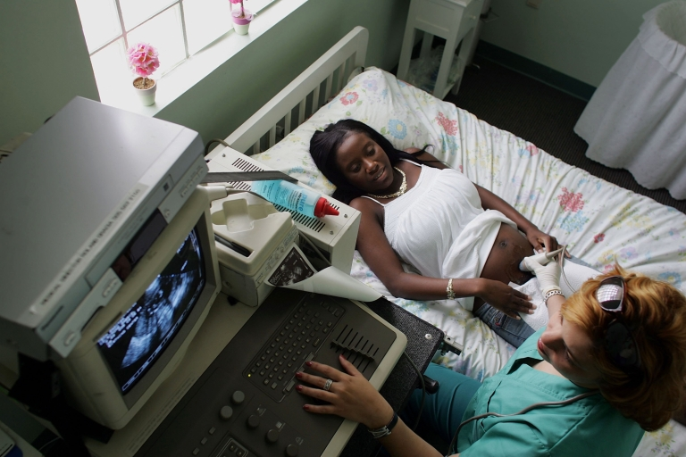 <p>A woman who is four months pregnant lies on a bed as an ultrasound machine captures images of her baby at the Birthing Center of South Florida October 12, 2006 in Florida City.</p>
