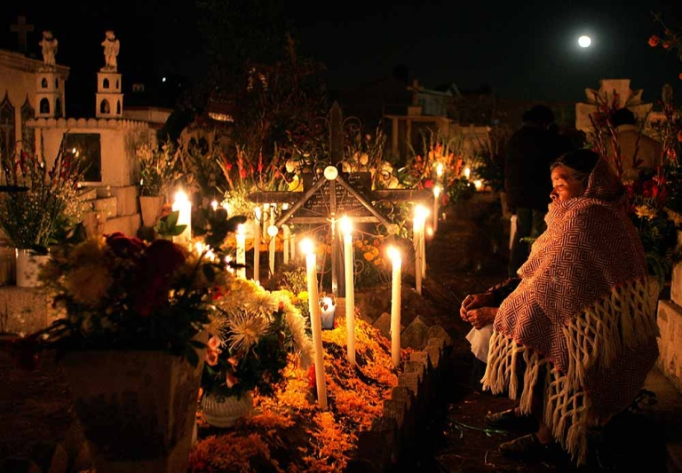 <p>A woman prays in front of a grave of a relative at the cemetery of San Gregorio Atlapulco, in Mexico City, November 2, 2006, during the Day of the Dead celebrations.</p>