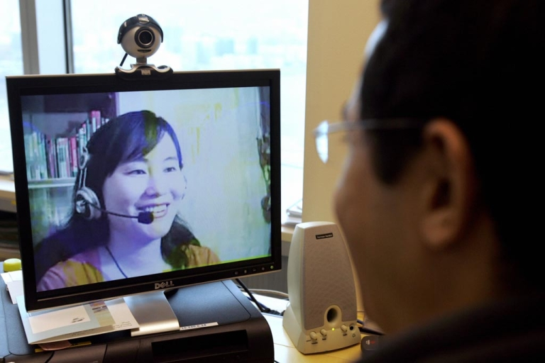 <p>A computer user in Hong Kong, looking at an image of online Mandarin teacher Lily Huang at her home on mainland China.</p>