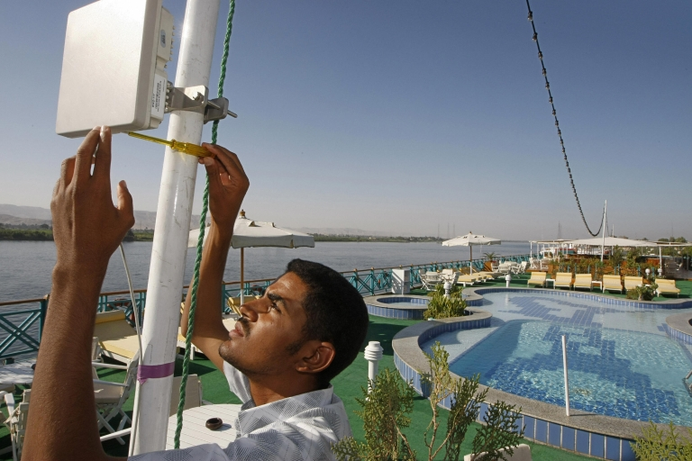 <p>A technician adjusts the position of an Internet router placed on a ship docked on the east bank of the River Nile in the city of Luxor in September 2007. The project funded by the United States Agency for International Development (USAID) and sponsored by the Egyptian Minister of Communications and Information targets the large tourism sector and offers open Internet connectivity in several cities of Egypt.</p>