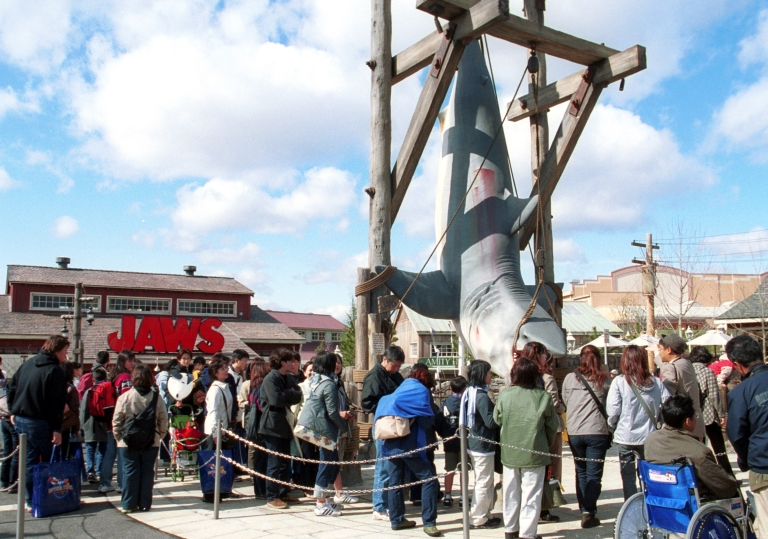 <p>Visitors crowd around a hanging shark display near the ride, themed after the Steven Spielberg motion picture