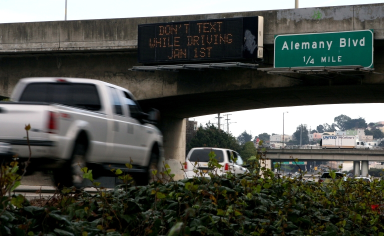 <p>Cars drive on Interstate 280 by a notification of a new texting while driving law December 29, 2008 in San Francisco, California.</p>