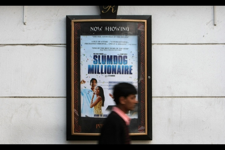 <p>An Indian man walks past a poster of the Oscar nominated film 'Slumdog Millionaire' in New Delhi on January 23, 2008.</p>