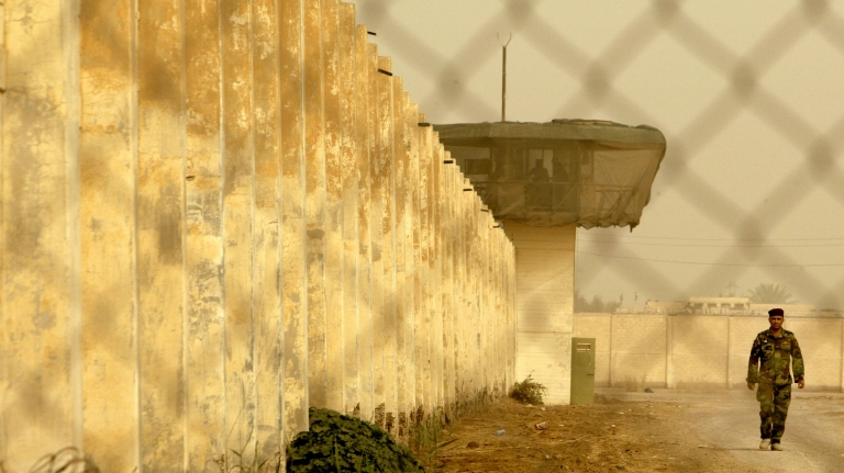 <p>An Iraqi Baghdad Central Prison security guard stands guard on February 21, 2009 outside the reopened Baghdad Central Prison in Abu Ghraib west of Baghdad, Iraq.</p>