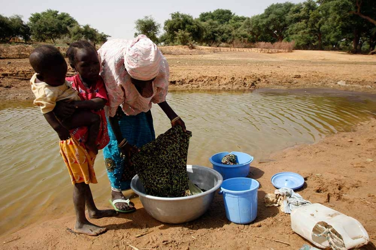 <p>Only 42% of Nigeriens have access to drinking water. The rest of the population goes directly to the source in rivers or natural stormwater reserves, and is exposed to the consumption of dirty water. A woman and her children washing ropes on natural stormwater on March 6, 2009 in Niamey, Niger.</p>