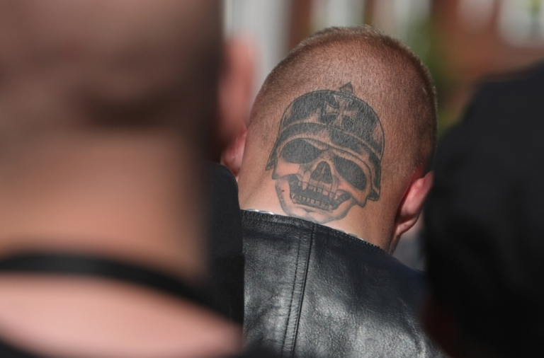 <p>Supporters of the German radical right-wing party, the NPD, including a man with the tatoo of a helemted skull on the back of his head, listen to speeches at a May Day celebration near NPD party headquarters on May 1, 2009 in Berlin, Germany.</p>