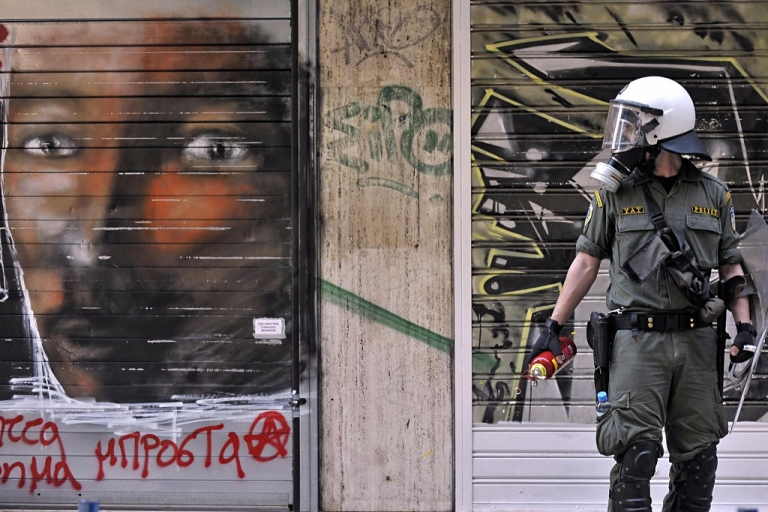 <p>A anti-riot police member stands next a graffiti during demonstrations in central Athens on May 9, 2009. Violence erupted after some 300 members of neo-Nazi group Chryssi Avghi, or Golden Dawn, gathered in Omonia square saying they wanted to liberate Athens and Greece from what they described as 'hordes of illegal immigrants'.</p>