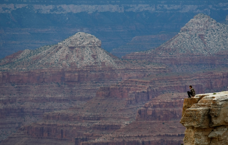 <p>A tourist sits on a precipice while gazing out into the Grand Canyon June 10, 2009 at sunset in the Grand Canyon National Park, Arizona.</p>