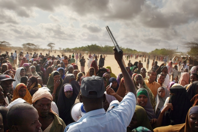 <p>A security officer keeps order for hundreds of people desperate to move to a less crowded refugee camp in Dadaab, the world's biggest refugee complex August 20, 2009 in Dadaab, Kenya.</p>
