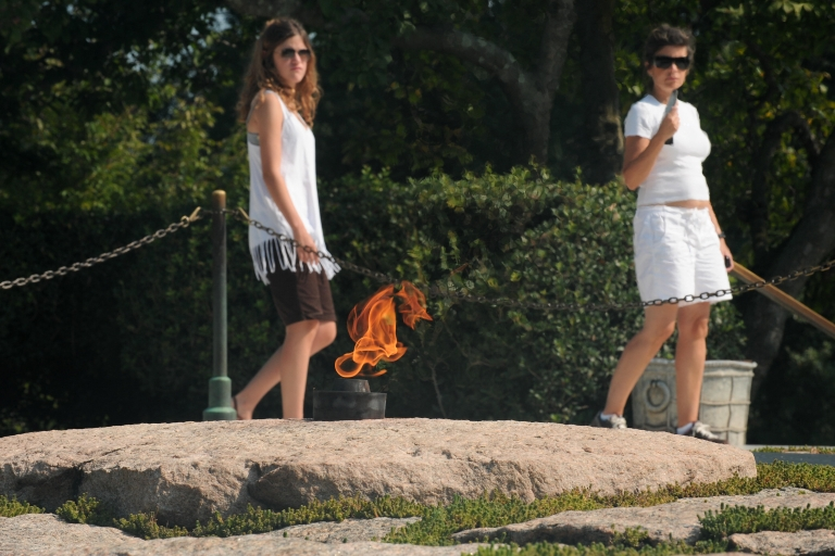 <p>Women walk past the flame burning on the grave of late US President John F. Kennedy at Arlington National Cemetery outside Washington, DC.</p>