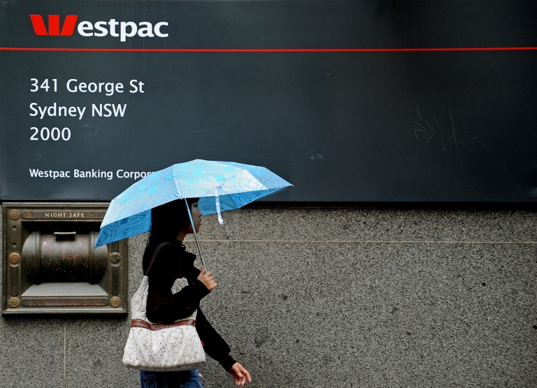 <p>A woman shelters under an umbrella as she walks past a Westpac Banking Corporation branch in central Sydney on October 26, 2009.</p>