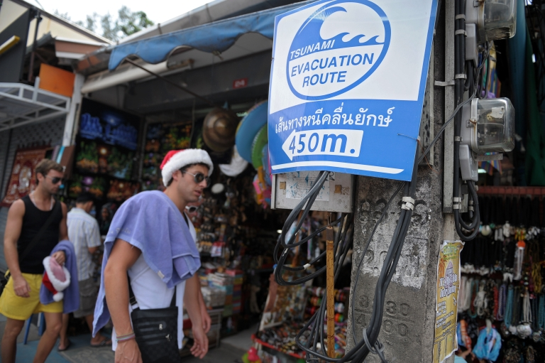 <p>Foreign tourists walk by a tsunami evacuation route sign at Patong beach on Thailand's southern island of Phuket on December 25, 2009.</p>