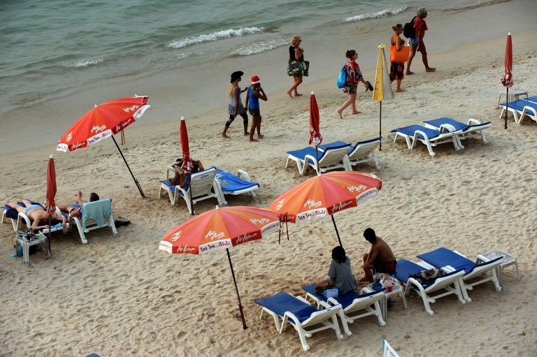 <p>Foreign tourists and locals walk by the sea at Patong beach on the southern island of Phuket on Dec. 25, 2009.</p>