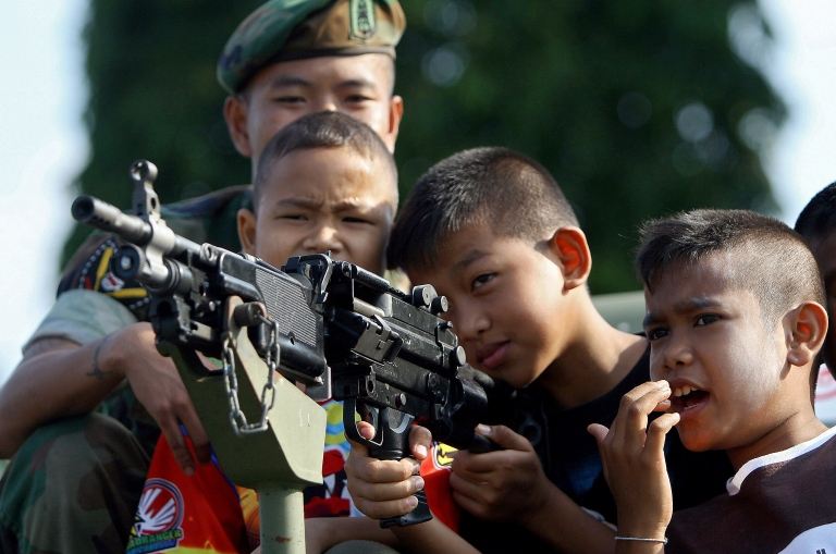 <p>Thai children aim an armored vehicle-mounted rifle as a soldier watches during a gathering at a Navy camp on the occasion of National Children's Day in Thailand's restive southern province of Narathiwat on January 9, 2010.</p>