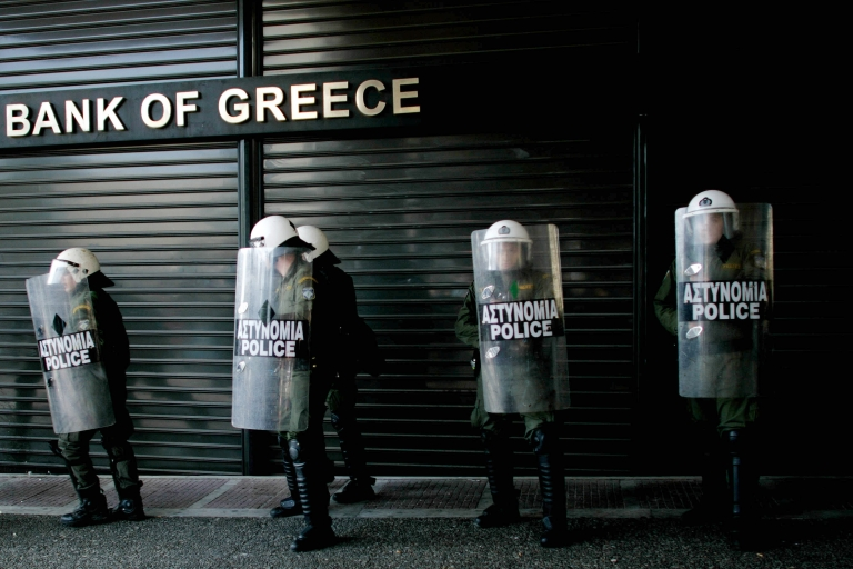<p>Riot police line up outside a bank during a 24-hour general strike. Greek banks received a 20 billion euro capital injection Monday.</p>
