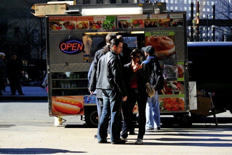 <p>People wait in line to buy thier lunch at a street food vendor cart in New York, March 8, 2010.</p>
