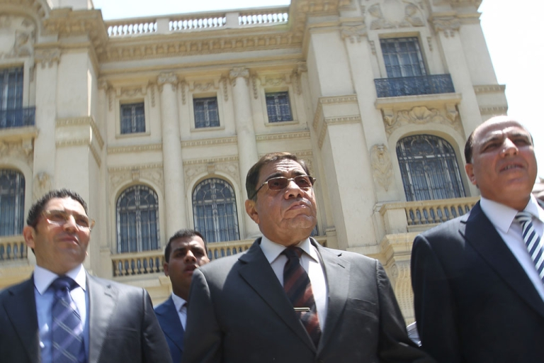 <p>Egypt's Prosecutor General Abdel Meguid Mahmud (C) leaves after speaking to journalists following his inspection of the Mohammed Mahmoud Khalil Museum (background) in Cairo on August 22, 2010.</p>