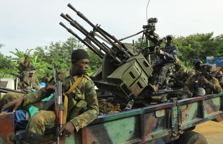 <p>Internationally recognized leader Alassane Ouattara's soldiers ride an armed vehicle in front of the Golf hotel in Abidjan, Ivory Coast, on April 5, 2011.</p>
