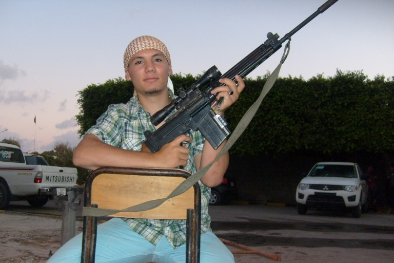 <p>Rebel fighter Abubakar Mustafa Awene, 18, poses with his weapon at the Deaf and Mute Brigade headquarters in Misrata.</p>