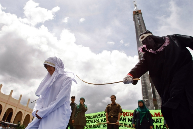 <p>A masked person canes Indonesian food seller Murni Amris for violating Islamic Shariah law outside a mosque in Jantho, Aceh province, Oct. 1, 2010.</p>