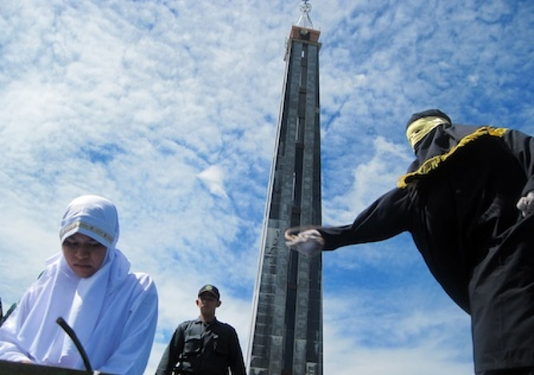 <p>A 17-year-old girl is caned by a sharia police at a mosque compound in the staunchly Muslim Aceh province where Islamic sharia laws have been adopted. She received eight lashes each after being caught having an extramarital kiss with a 24-year-old man.</p>