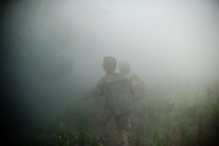 <p>Fog of War: Soldiers from 10th Mountain Division make their way through thick smoke after blasting a mud brick wall apart in Kandahar.</p>