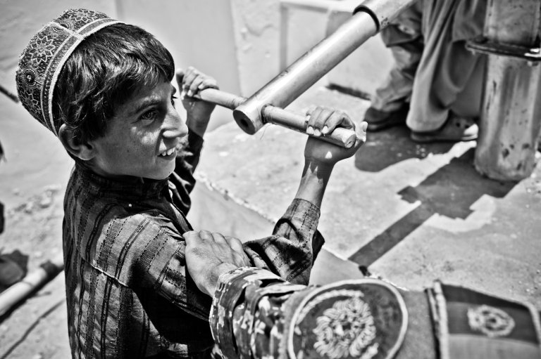 <p>Outside a mosque in Zhari District, a boy speaks with Afghan troops while pumping water from a well.</p>