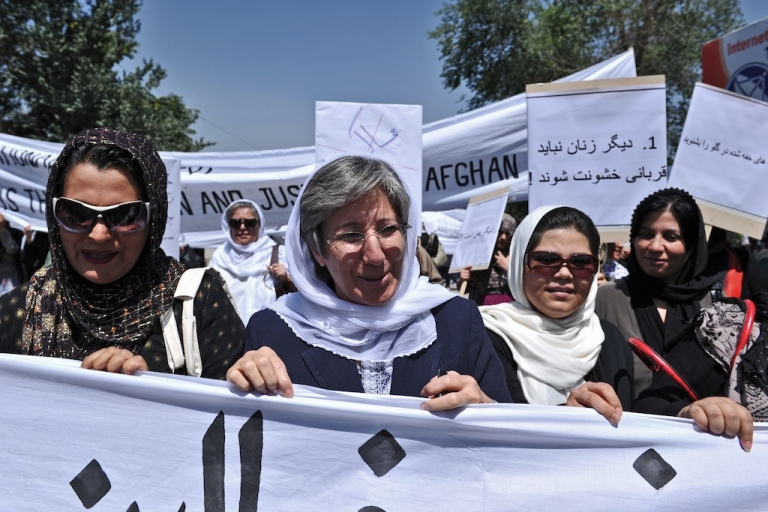 <p>Afghanistan head of Human Rights Commision Seema Samar (C) marches with Afghan women to protest the recent public execution of a young woman for alleged adultery, in Kabul on July 11, 2012. Dozens of Afghan women's rights activists took to the streets to protest the recent public execution of a young woman for alleged adultery, which was captured in a horrific video.</p>