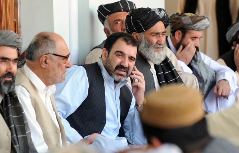<p>Ahmed Wali Karzai (C) talks on the phone as he sits with supporters celebrating the re-election victory of his brother President Hamid Karzai in Kandahar on November 3, 2009.</p>