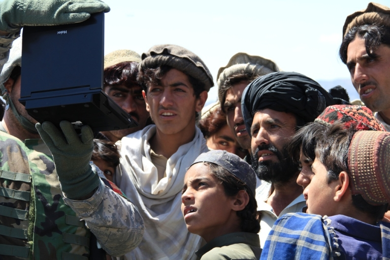 <p>Afghan villagers watch a U.S. propaganda film on a portable DVD player that attempts to explain why the U.S. military is in Afghanistan.</p>