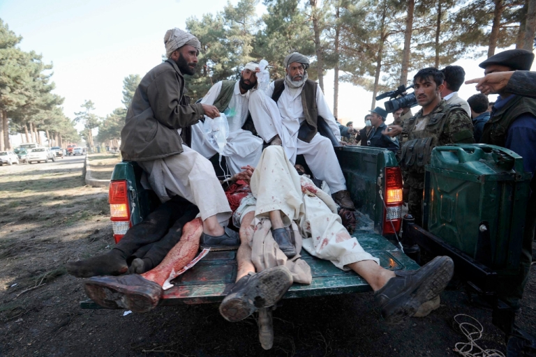 <p>Afghan men sit on the back of a police vehicle laden with the victims of a suicide bomb attack in Herat Province on April 10, 2012. At least nine people were killed when two suicide bombers rammed their vehicle into a local government compound near Afghanistan's western city of Herat on on April 10, police and witnesses said.</p>