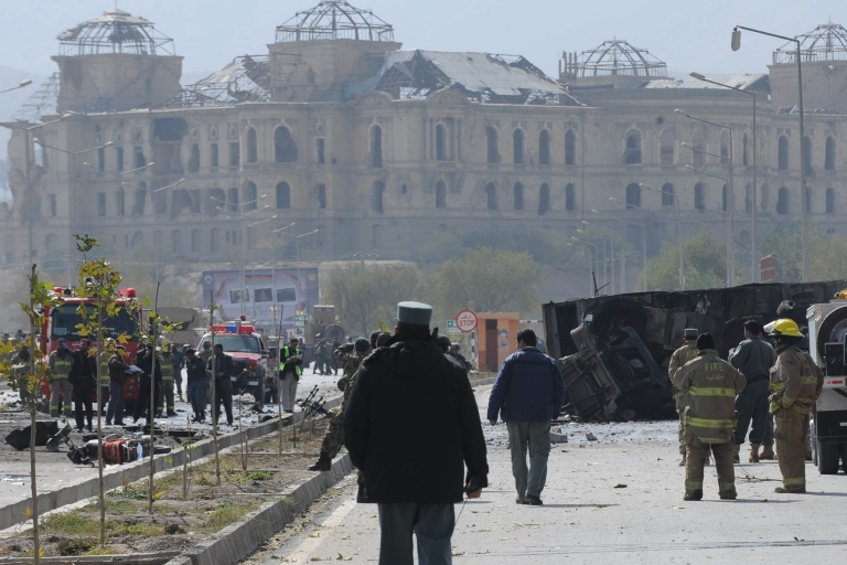 <p>Afghanistan's security force and rescue personnel inspect the site of a suicide attack near the Darul Aman palace (back) in Kabul on October 29, 2011. At least 17 people, including foreign forces, were killed when a Taliban car bomber struck a US-run NATO convoy traveling through the Afghan capital Kabul.</p>