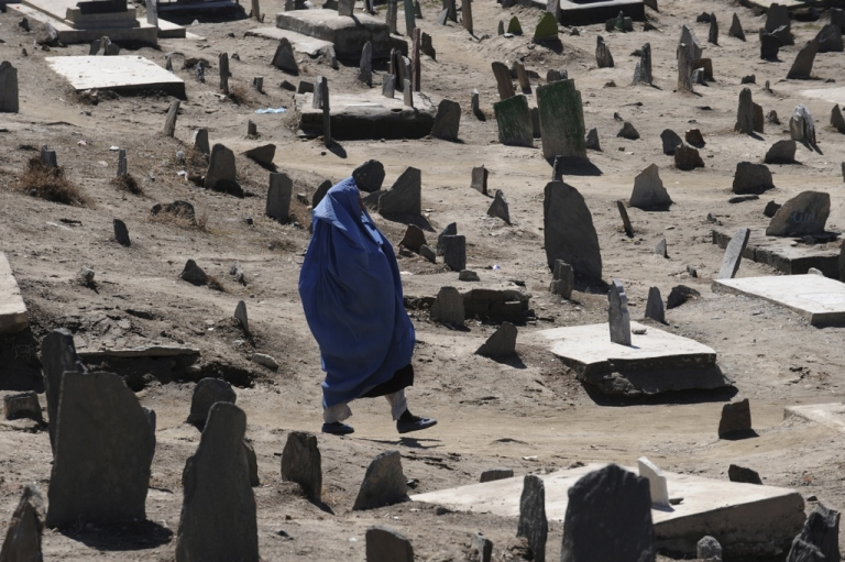 <p>A burqa-clad Afghan woman walks in a Muslim cemetery in Kabul on March 9, 2011. The impact of the Afghanistan war on ordinary people was laid bare on March 9 by UN figures showing a 15 percent increase in the number of civilians killed last year, the highest annual toll since 2001.</p>