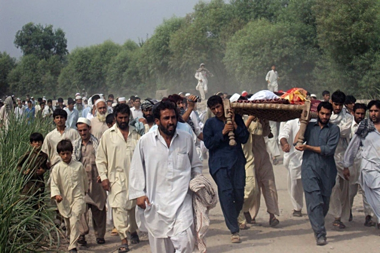 <p>Afghan men shout anti-U.S. slogans as they carry the bodies of two people killed in a night raid in the eastern city of Jalalabad on Aug. 18. 2010.</p>