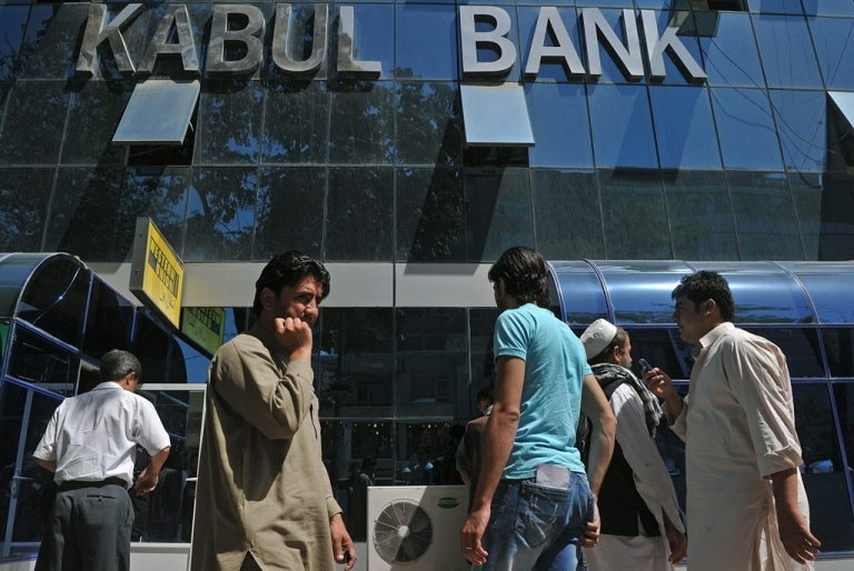 <p>Afghan pedestrians walk past the main branch of The Kabul Bank in Kabul on Sept. 4, 2010.</p>