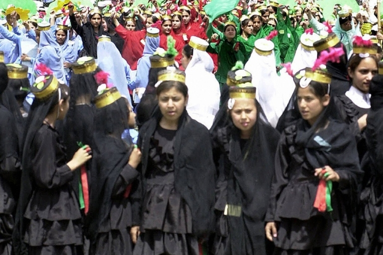 <p>Afghan schoolgirls perform under a poster of Ahmad Shah Massoud at an earlier, and happier, Victory Day celebration in 2004.</p>
