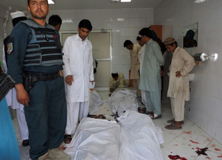 <p>Afghan policeman and civilians gather at a hospital morgue holding the bodies of suicide bombing victims in Khost on June 20, 2012.</p>