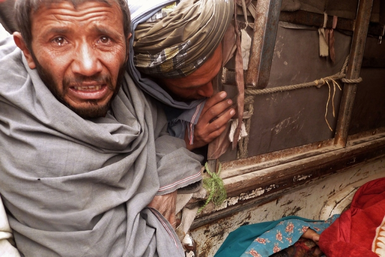 <p>A mourner cries over the bodies of Afghan civilians, allegedly shot by a rogue US soldier, seen loaded into the back of a truck in Alkozai village of Panjwayi district, Kandahar province on March 11, 2012.</p>