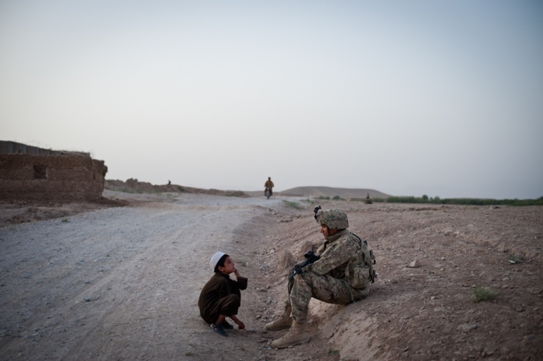 <p>Sgt. Oscar Cuellar and an Afghan boy consider each other for a moment in the outskirts of Qalat, the capital of Zabul Province.</p>