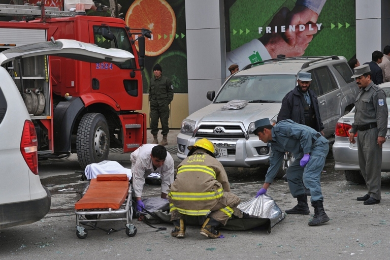 <p>Afghan rescue workers outside Finest supermarket after a suicide bombing attack on Jan. 28, 2011.</p>