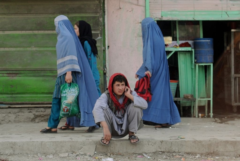<p>An Afghan man speaks on a phone as burqa-clad women walk past on a street in Kabul on May 20, 2011.</p>