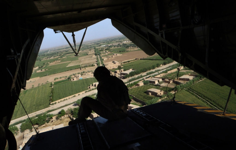 <p>A member of the U.S. Marine helicopter CH 53 crew sits at the back door as it flies over Marjah district in Helmand Province, Afghanistan, on May 3, 2011.</p>