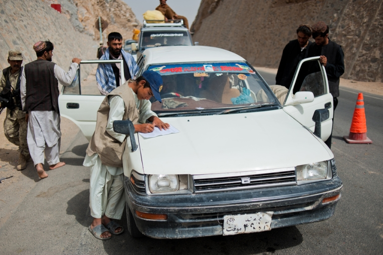 <p>At a busy traffic checkpoint, cars traveling from Arghandab into Kandahar City are searched for weapons.</p>