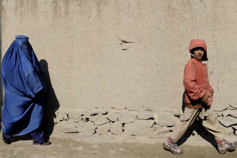 <p>A burqa-clad Afghan woman with her son walks in Kabul on Feb. 16, 2011.</p>