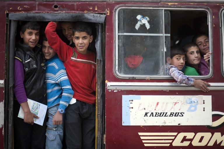 <p>Afghan children ride a bus after taking part in a performance to celebrate the second