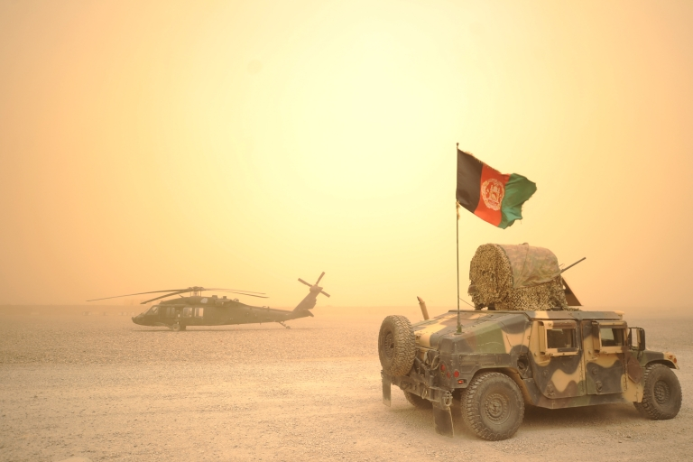 <p>An Afghan National Army Humvee jeep drives past a U.S. army Black Hawk helicopter from Alpha Company 7-101 AVN during a sandstorm at FOB Wilson in Kandahar province in southern Afghanistan on March 27, 2011. Around 140,000 foreign troops are deployed in Afghanistan within the U.N.-mandated, NATO-led, International Security Assistance Force (ISAF) and the US-led coalition Operation Enduring Freedom, which overthrew the Taliban in late 2001.</p>