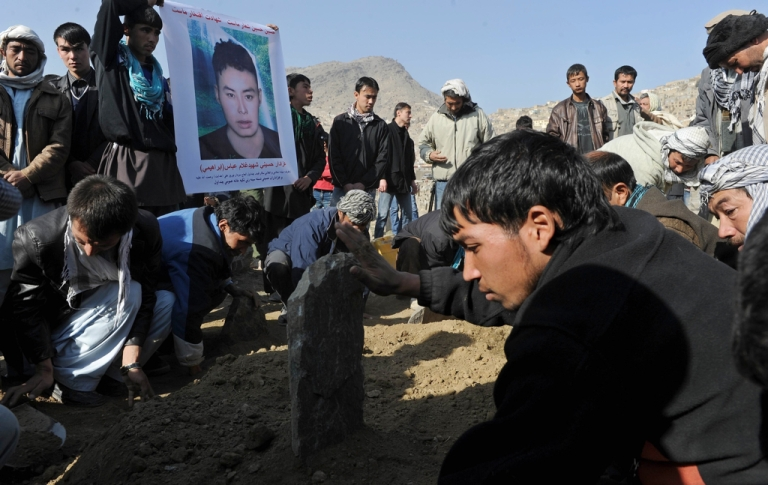 <p>Afghan men bury victims of a bomb attack against Shiite Muslims outside the Karti Sakhi Shrine in Kabul on December 7, 2011.</p>
