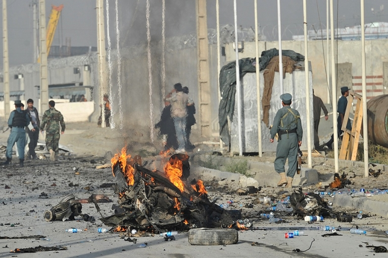 <p>Afghanistan police and officials investigate the site of a suicide attack in Kabul on Sept. 18, 2012. A suicide bomber blew himself up alongside a minivan carrying foreigners on a major highway leading to the international airport in the Afghan capital, police said, killing at least 10 people, including nine foreigners.</p>