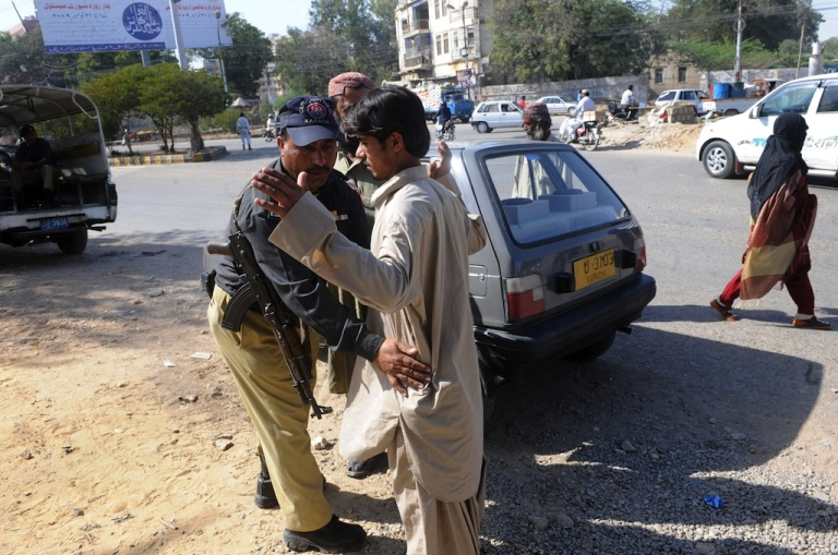 <p>A Pakistani policeman searches a pedestrian at a security check point in Karachi on February 16, 2010. At the time, Pakistan's Interior Minister Rehman Malik branded as 'propaganda' reports that the top Taliban military commander Mullah Abdul Ghani Baradar had been arrested in a joint Pakistani-US spy operation.</p>