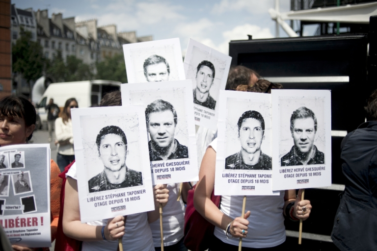 <p>People hold placards with pictures of the two French journalists kidnapped by the Taliban in Afghanistan in December 2009, on June 29, 2011 in Paris, during a demonstration prior to the announcement of their release.</p>